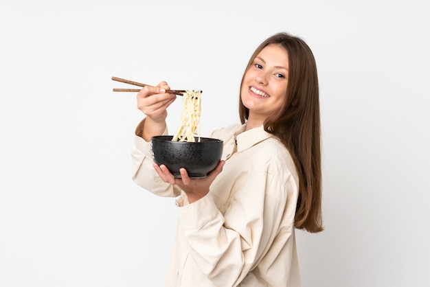 Teenager caucasian girl isolated on white wall holding a bowl of noodles with chopsticks