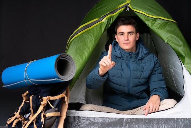 黒の背景に分離されたキャンプの緑のテントの中の10代の白人男性イライラして前方を向く