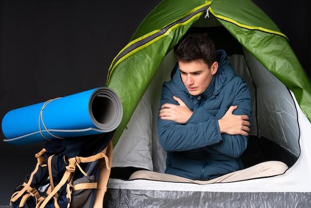 캠핑 녹색 텐트 안에 십대 백인 남자는 검은 동결에 고립