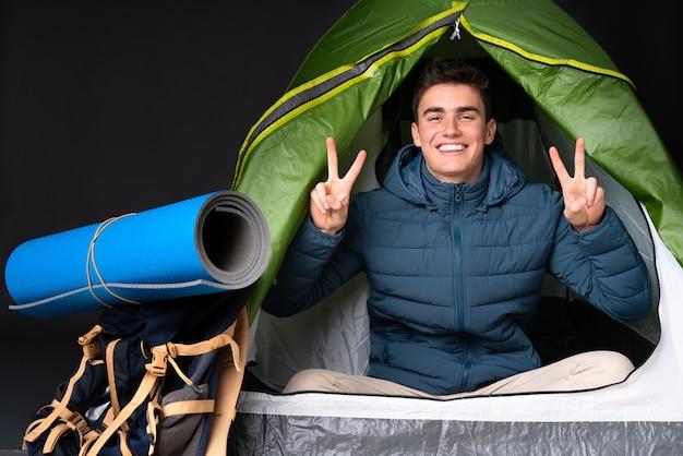 両手で勝利のサインを示す黒に分離されたキャンプの緑のテントの中の10代の白人男性