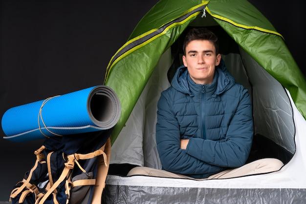 Подросток кавказский человек в зеленой палатке на черной стене, расстроен