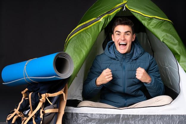 悪い状況にイライラした黒い壁にキャンプの緑のテントの中の10代の白人男性