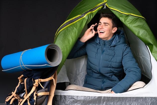 Кавказский подросток в зеленой палатке на черной стене, ведя разговор с мобильным телефоном