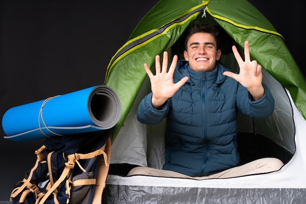 Teenager caucasian man inside a camping green tent isolated on black counting eight with fingers