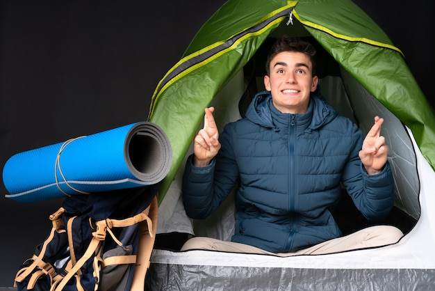 Teenager caucasian man inside a camping green tent isolated on black wall with fingers crossing and wishing the best