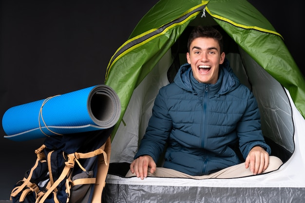 Teenager caucasian man inside a camping green tent isolated on black with surprise facial expression