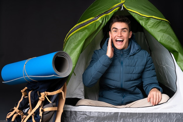 Teenager caucasian man inside a camping green tent isolated on black with surprise and shocked facial expression