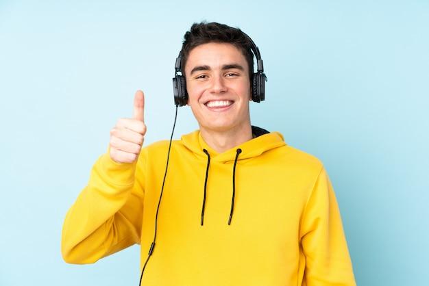 Подросток кавказских человек, изолированные на фиолетовом фоне прослушивания музыки и с пальца вверх