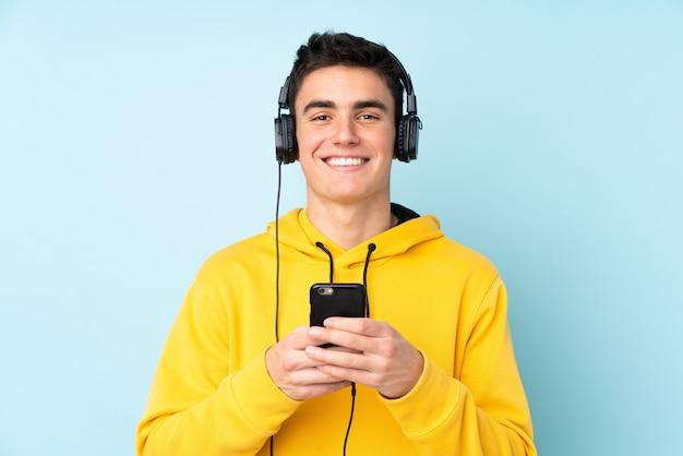 Подросток кавказских человек, изолированных на фиолетовом фоне прослушивания музыки с мобильного телефона и глядя спереди
