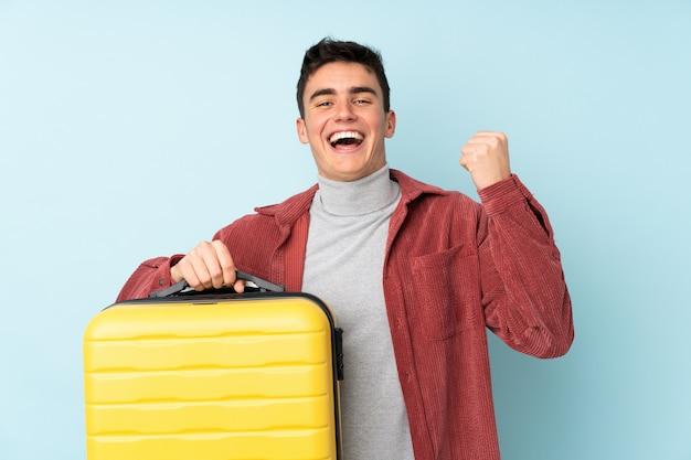 Человек подростка кавказский изолированный на пурпуре в каникулах с чемоданом перемещения