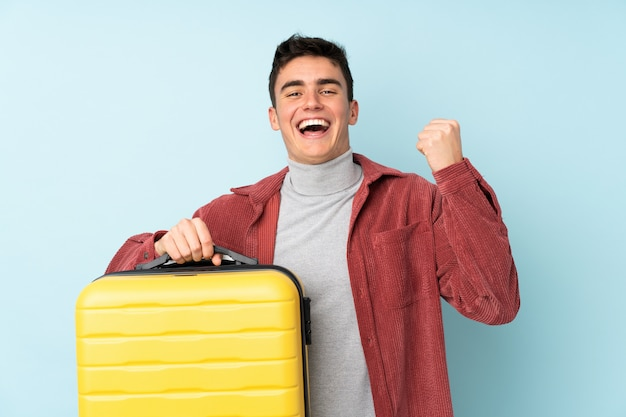 Teenager caucasian man isolated on purple in vacation with travel suitcase