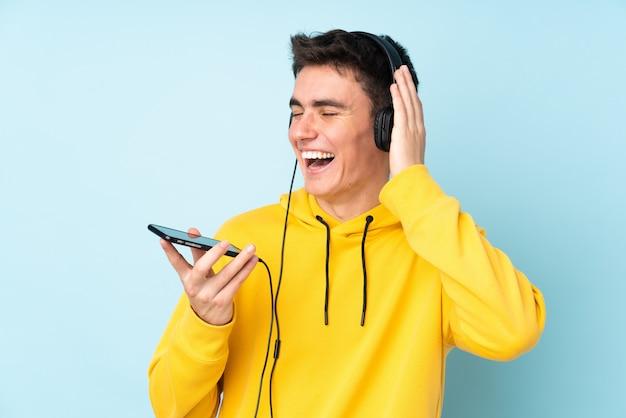 Подросток кавказский человек на пурпурной стене прослушивания музыки с мобильного телефона и пения
