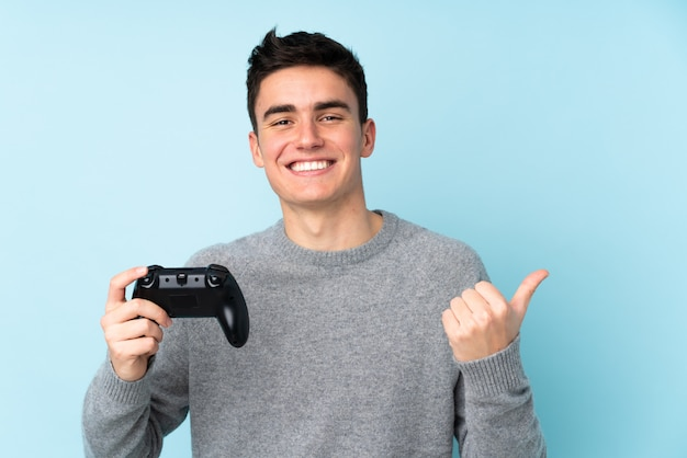 Teenager caucasian man playing with a video game controller isolated on blue background pointing to the side to present a product