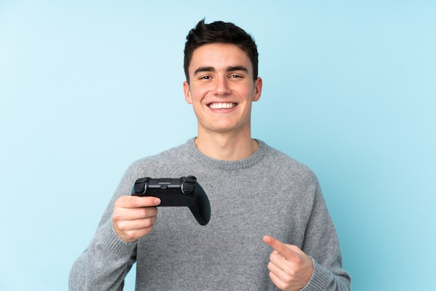 Teenager caucasian man playing with a video game controller isolated on blue and pointing it