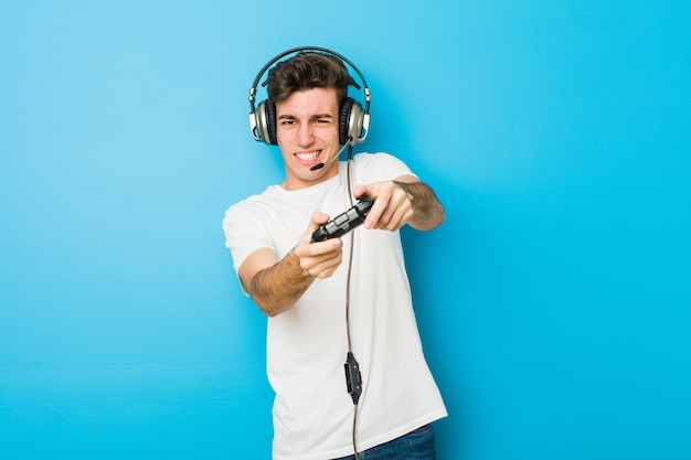 Teenager caucasian man using headphones and game controller
