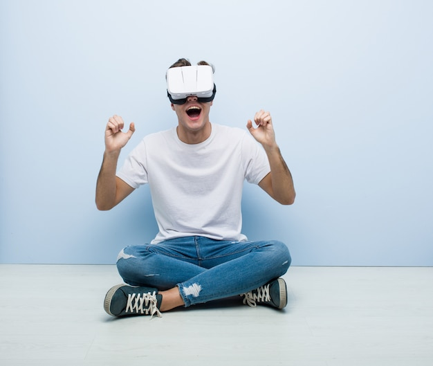 Teenager caucasian man using a virtual reality glasses sitting floor