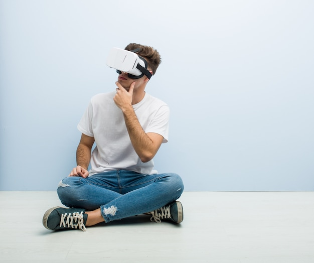 Teenager caucasian man using a virtual reality glasses sitting on the floor