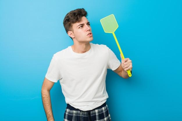 Подросток кавказский человек в пижаме и держит мухобойку Premium Фотографии