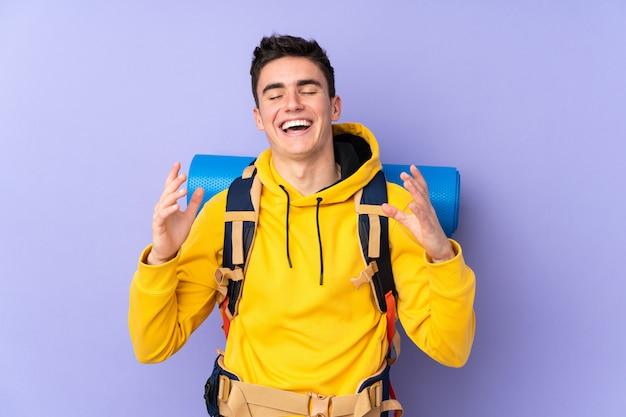 보라색 배경 웃음에 고립 된 큰 배낭 십 대 백인 산악인 남자