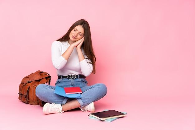 愛らしい表現で睡眠ジェスチャーを作るピンクの壁に分離された床に座っている10代の白人学生の女の子