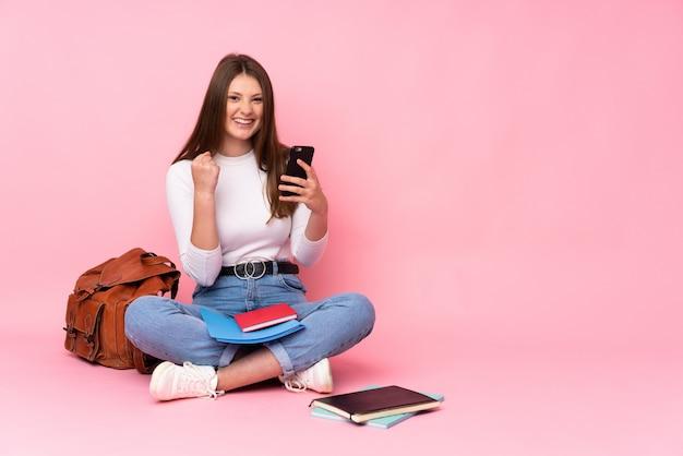 勝利位置に電話でピンクに分離された床に座っている10代の白人学生の女の子