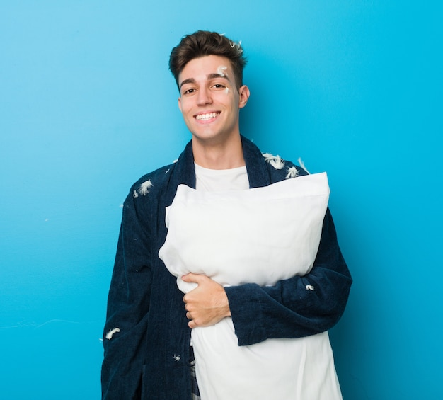 Teenager caucasian tired man holding a pillow
