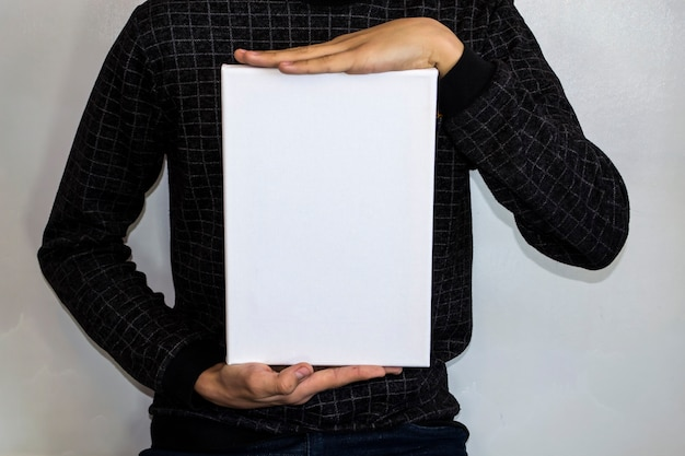 A teenager in a checkered jacket holds a white rectangle for your advertising