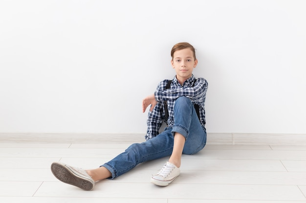 Teenager, children and fashion concept - fashionable boy sitting on floor over white wall