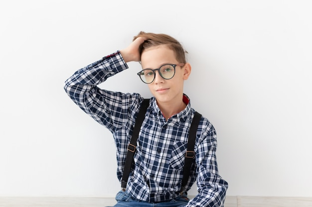 Teenager, children and fashion concept - portrait of kid dressed in plaid shirt posing over white wall