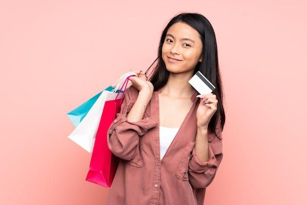 ショッピングバッグとクレジットカードを保持しているピンクで隔離のティーンエイジャーの中国の女の子