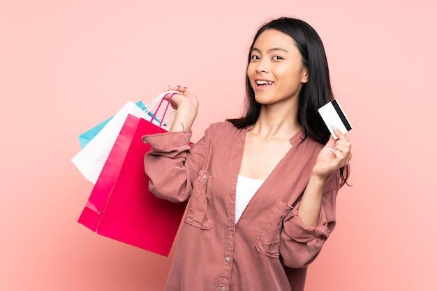 ショッピングバッグとクレジットカードを保持しているピンクの壁に分離された10代の中国の女の子