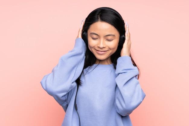 ピンクに分離された10代の中国の女の子