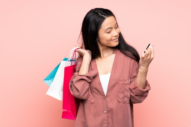 Teenager chinese girl on pink wall holding shopping bags and a credit card