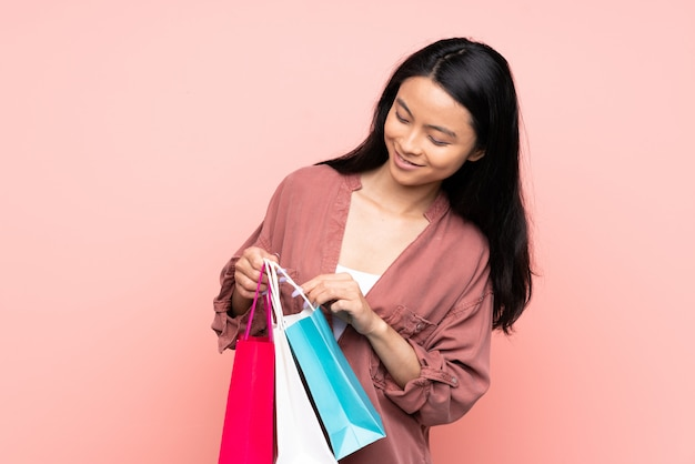 Teenager chinese girl on pink wall holding shopping bags and looking inside it