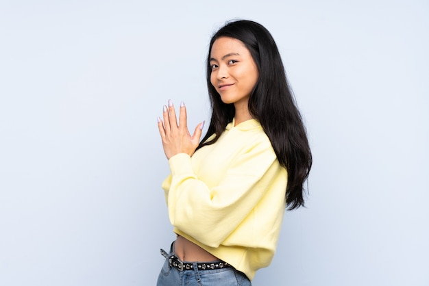 Teenager chinese woman on blue wall scheming something