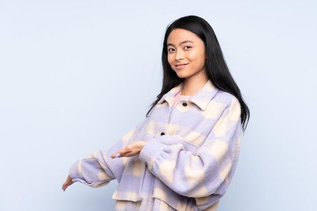 来るように誘うために横に手を伸ばして青い上に隔離された10代の中国人女性