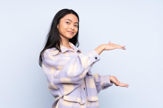 広告を挿入するためにコピースペースを保持している青に分離された10代の中国人女性