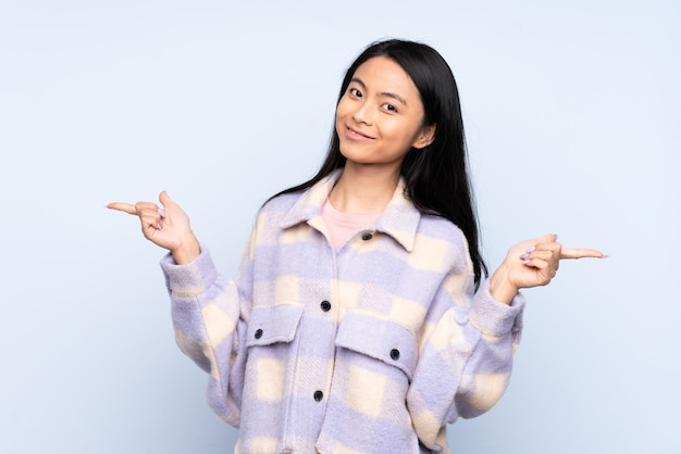 側面に青い人差し指で隔離され、幸せな10代の中国人女性