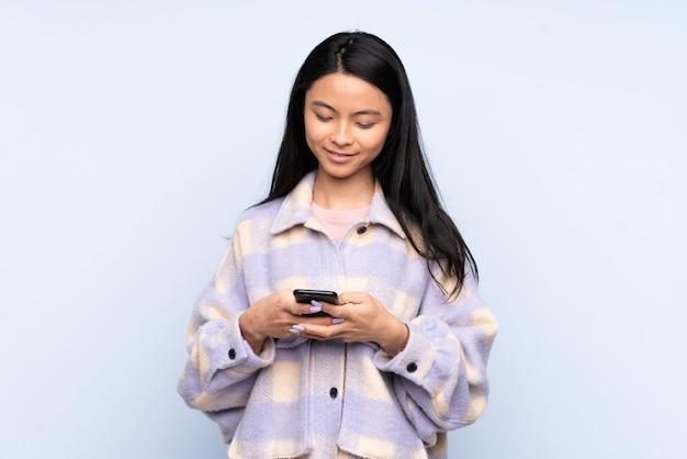 携帯電話でメッセージを送信する青に分離された10代の中国人女性