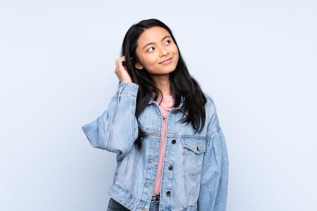アイデアを考えて青い壁に分離された10代の中国人女性