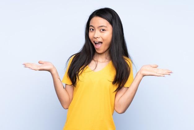 ショックを受けた表情で青に分離された10代の中国人女性