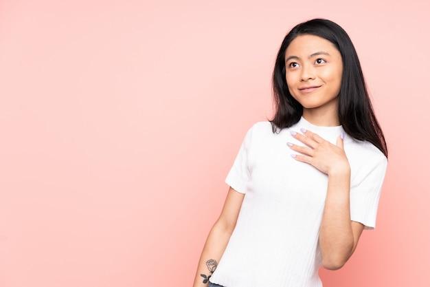 Подросток китаянка, изолированных на розовом фоне, глядя вверх, одновременно улыбаясь