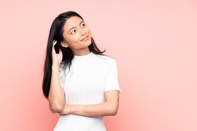 Китайская женщина-подросток изолирована на розовом, думая об идее