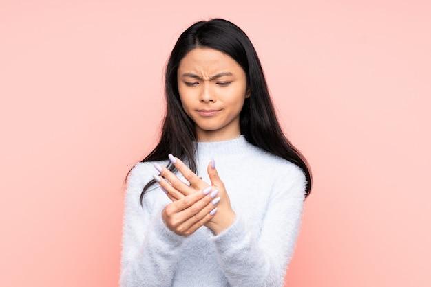 Подросток китаянка на розовой стене страдает от боли в руках