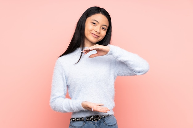 Teenager chinese woman isolated on pink background holding copyspace imaginary on the palm to insert an ad