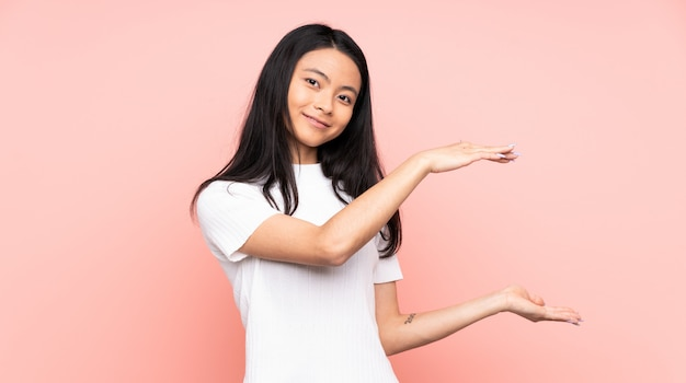 Teenager chinese woman isolated on pink wall holding copyspace to insert an ad