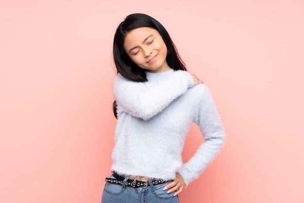 Подросток китаянка на розовой стене страдает от боли в плече за усилия