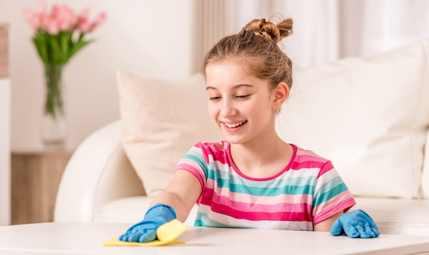 Teenager cleaning table in living room