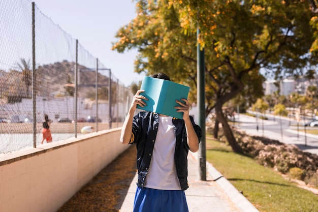 Teenager closing face by book
