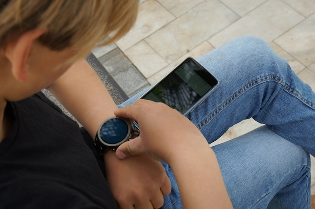 Teenager connecting his samrtwatch with his smartphone